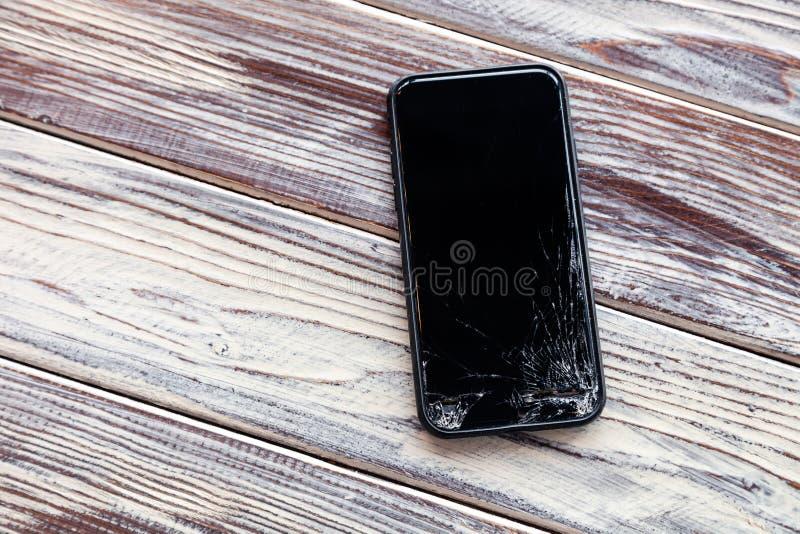 Ð ¡ loseup有说谎在木桌上的残破的屏幕玻璃的黑色智能手机 落下的电话,残破的小配件,电子的概念 库存照片