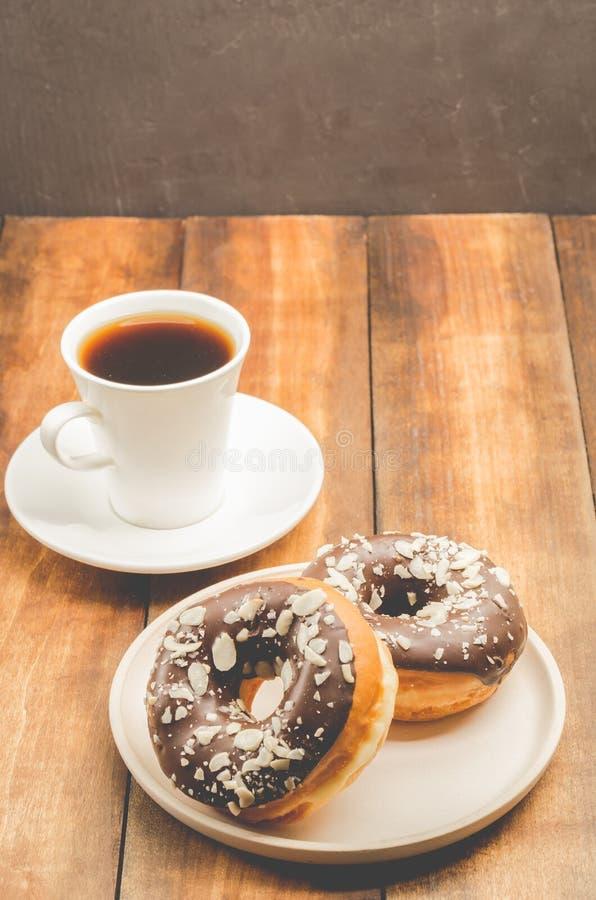 Ð ¡ offee przerwa Biała filiżanka z czarną kawą i Donat w czekoladowym glazerunku Drewniany t?o obraz royalty free