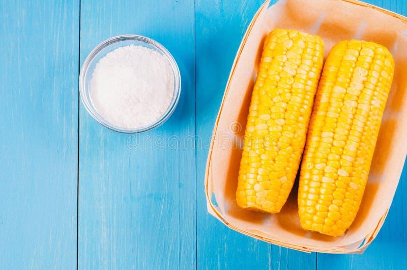 Ð-¡ Orn mit Salz Beschneidungspfad eingeschlossen Gelber Mais im kleinen Korb- und Salzglas auf blauem hölzernem Hintergrund lizenzfreie stockfotografie
