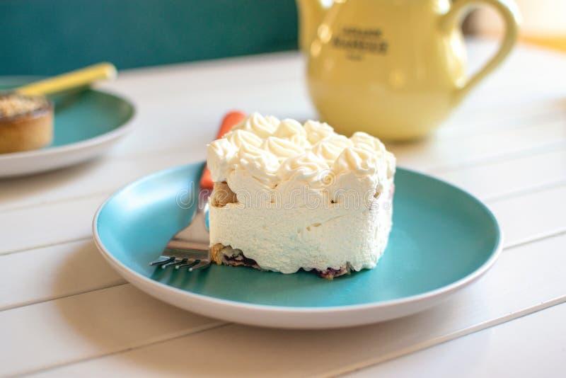 Ð ¡ riemcake op blauwe plaat met vork, gele theepot en groene kop Heerlijke witte dessert en thee in koffie Een stuk van kokosnoo royalty-vrije stock foto
