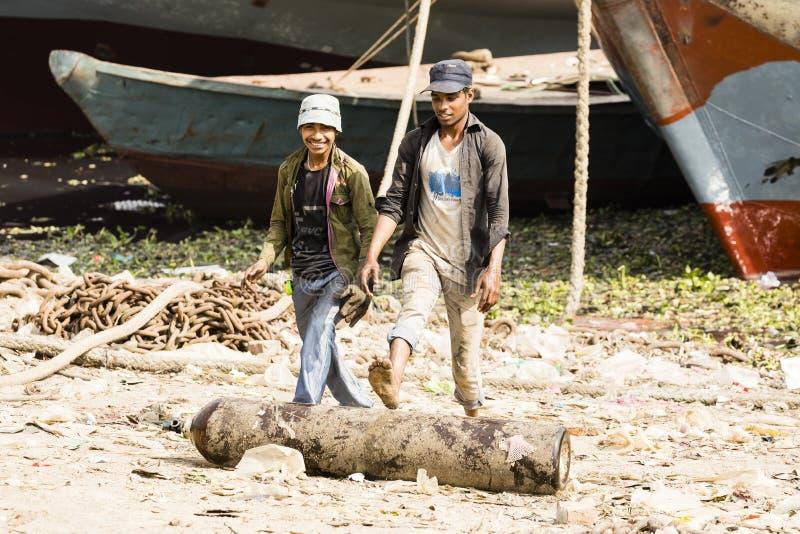 Дакка, Бангладеш, 24-ое февраля 2017: 2 работника на верфи в Дакка Бангладеше используют их ноги для того чтобы свернуть баллон стоковая фотография