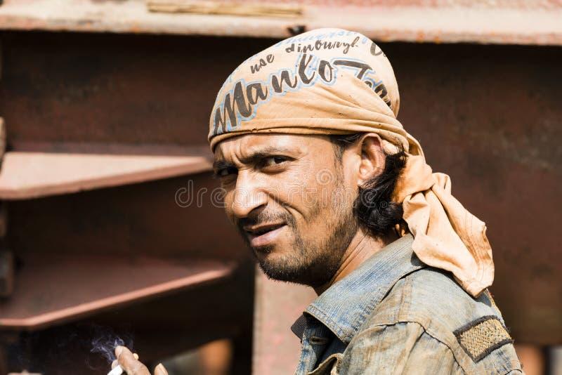 Дакка, Бангладеш, 24-ое февраля 2017: Работник на доке корабля в Бангладеше курит сигарету стоковое изображение