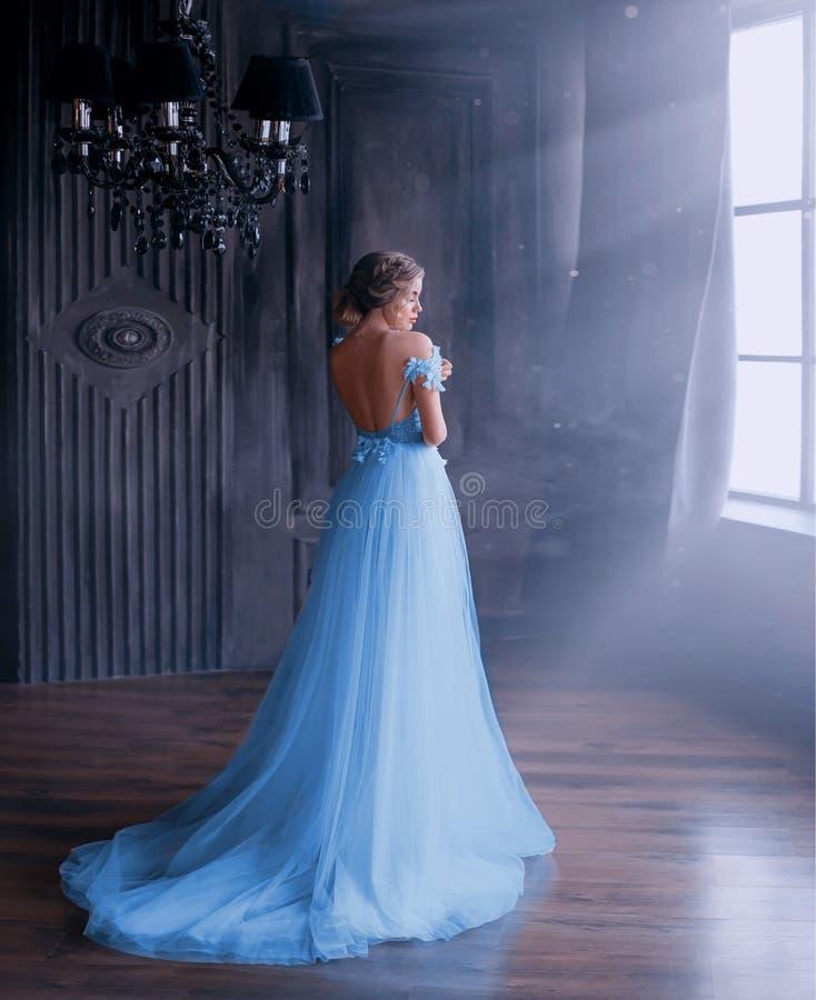 Дама в длинном голубом винтажном платье с поездом и открытых задних стойках с задней частью к камере комната с большими окнами с стоковые фотографии rf