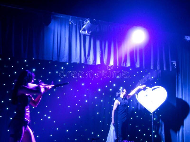 Дама снимает арбалет на цели сердца форменной во время шоу стоковая фотография