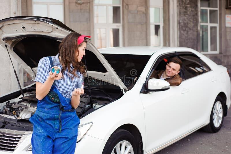 Двигатель автомобиля милой привлекательной девушки рассматривая на ремонтной мастерской ремонта автомобилей стоковое изображение