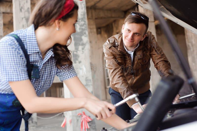 Двигатель автомобиля милой привлекательной девушки рассматривая на ремонтной мастерской ремонта автомобилей стоковая фотография