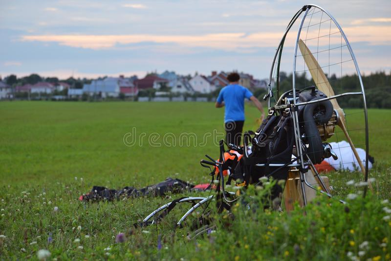 Двигатель мотора и параплана перед летанием на зеленой траве, подготавливая для взлета в поле стоковая фотография rf