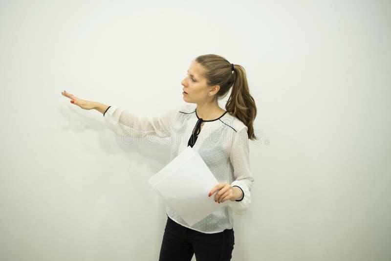 Девушка брюнета на белой предпосылке говорит и указывает на стену с ее правой рукой стоковые фото