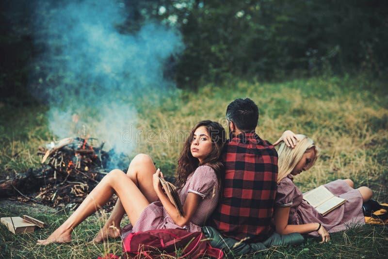 Девушка брюнета полагаясь на ее парне пока книга чтения Поверните назад парня смотря лагерный костер соедините детенышей влюбленн стоковое фото rf