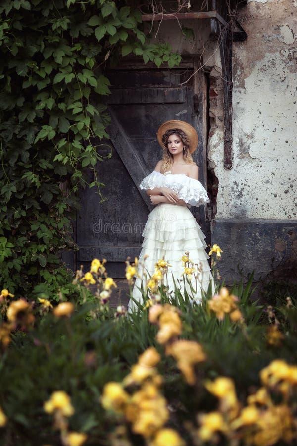 Девушка в винтажном платье Старая серая дверь стоковое фото
