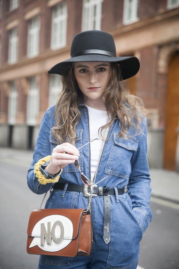 Девушка в голубом комбинезоне джинсовой ткани и широк-наполненные до краев стойки шляпы в середине дороги стоковое изображение rf