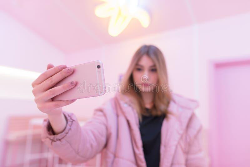 Девушка в розовых одеждах делает фото на розовом смартфоне в розовой комнате Розовая жизнь Фокус на вашем телефоне стоковое фото rf