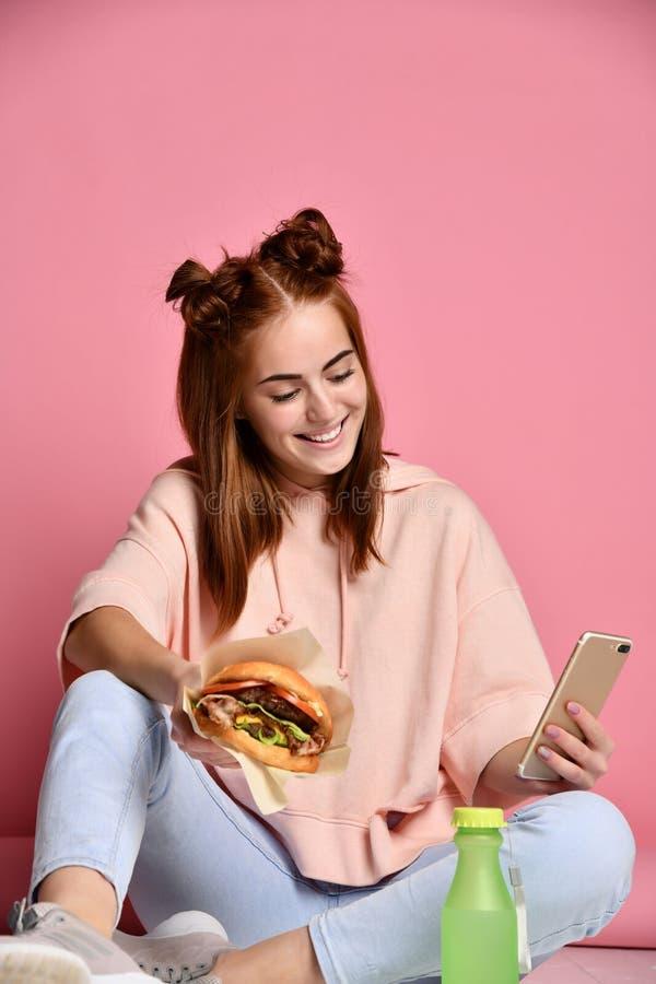 Девушка есть бургер и смотря телефон Концепция жизни молодости стоковая фотография rf