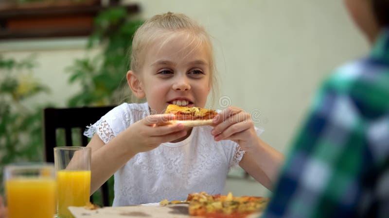 Девушка есть пиццу с братом в кафе, празднуя день рождения, любимая еда стоковое изображение