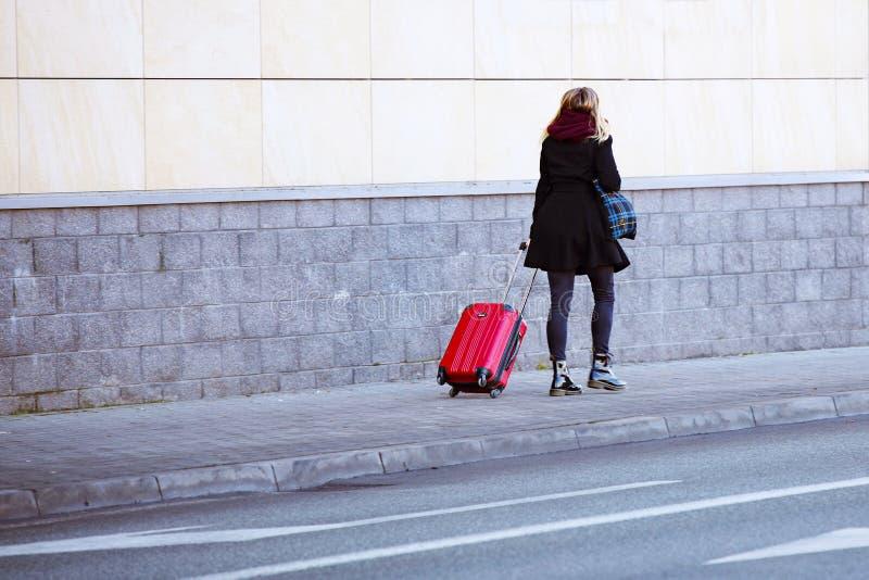 Девушка идет на тротуар с красной сумкой перемещения на колесах Турист багажа молодой в современном стильном чемодане Путешествен стоковое фото rf