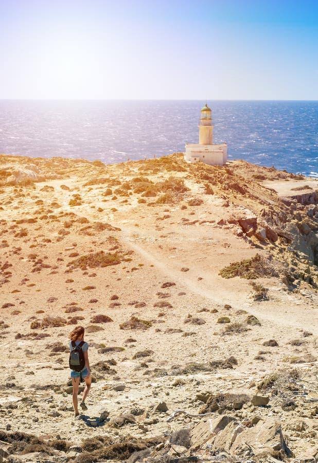 Девушка идя к белому маяку в национальном парке Родосе Prasonisi, Греции стоковое изображение rf