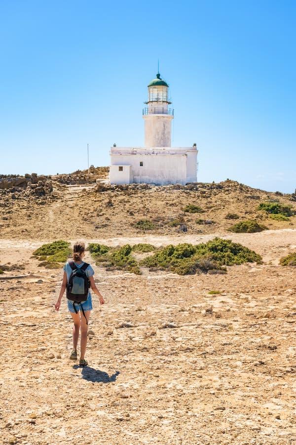 Девушка идя к белому маяку в национальном парке Родосе Prasonisi, Греции стоковые фотографии rf