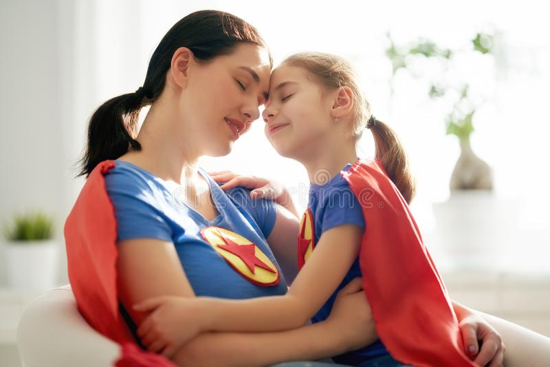 Девушка и мама в костюме супергероя стоковое фото rf