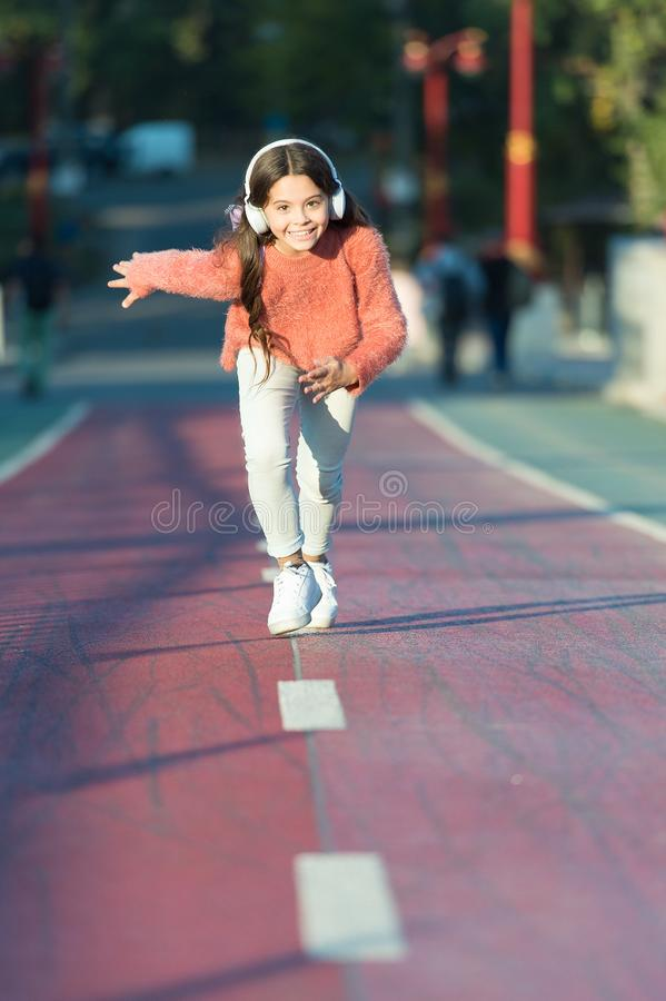 Девушка милая с наушниками Меньший ребенок насладиться деятельностью Ход ребенк идя в музыке парка слушая Музыка заполняет меня с стоковое изображение rf