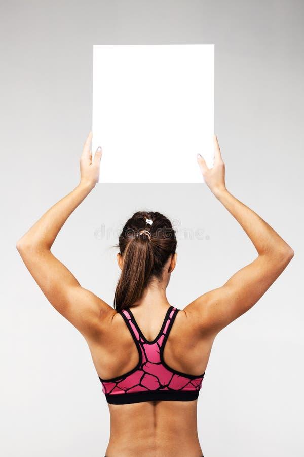 Девушка пригонки держа пустой белый квадрат стоковые фотографии rf