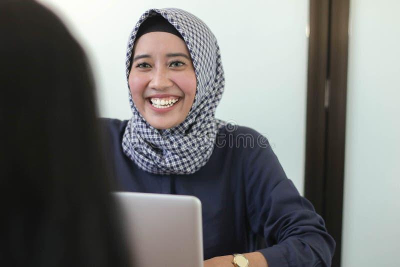 Девушка профессионального молодого hijab мусульманская работая с ноутбуком, молодой мусульманский интервьюировать женщины стоковые фото