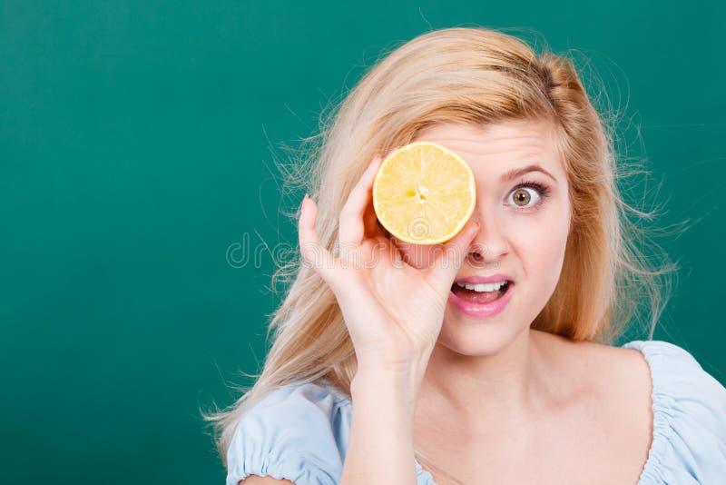 Девушка покрывая ее глаз с цитрусовыми фруктами лимона стоковое фото rf