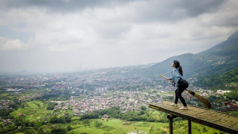 Девушка действуя с веником в небе стоковое фото