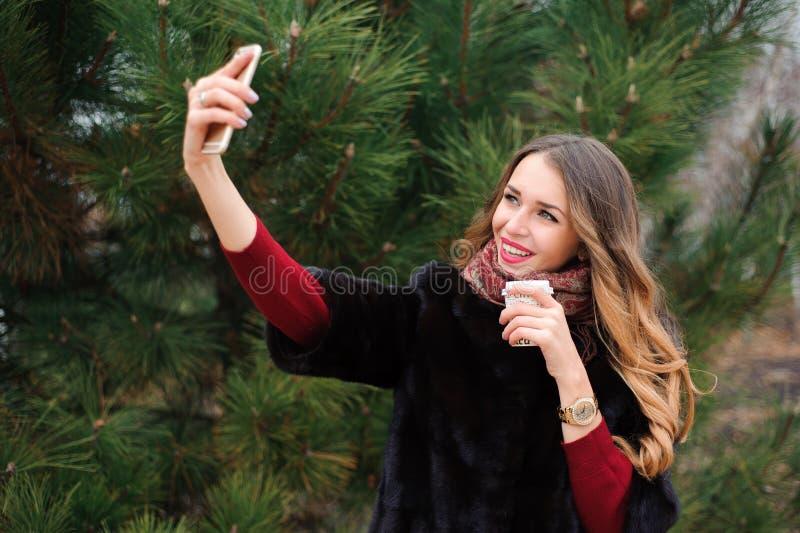 Девушка делая selfie в парке осени, привлекательной женщине идя в парк во дне осени стоковое изображение rf