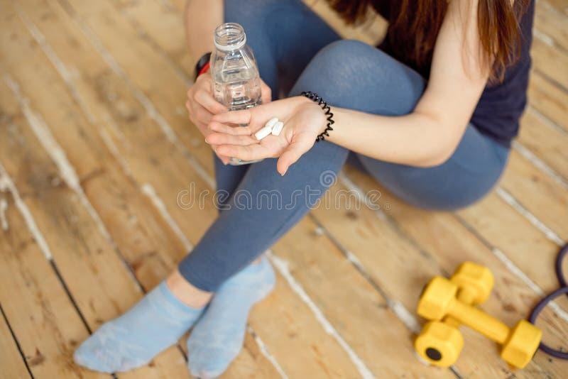 Девушка спорт в голубой рубашке и голубых гетры сидит на поле и держит в ее дополнениях спорт рук в капсулах стоковое фото