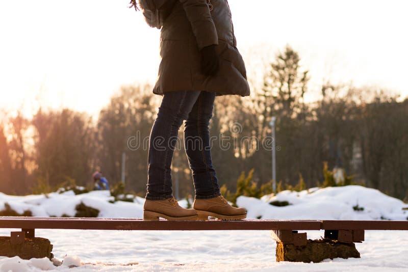 Девушка стоит на стенде во дне зимы солнечном на запачканном ² backgrounÐ в теплом outerwear Концепция принимать решениее, indece стоковая фотография