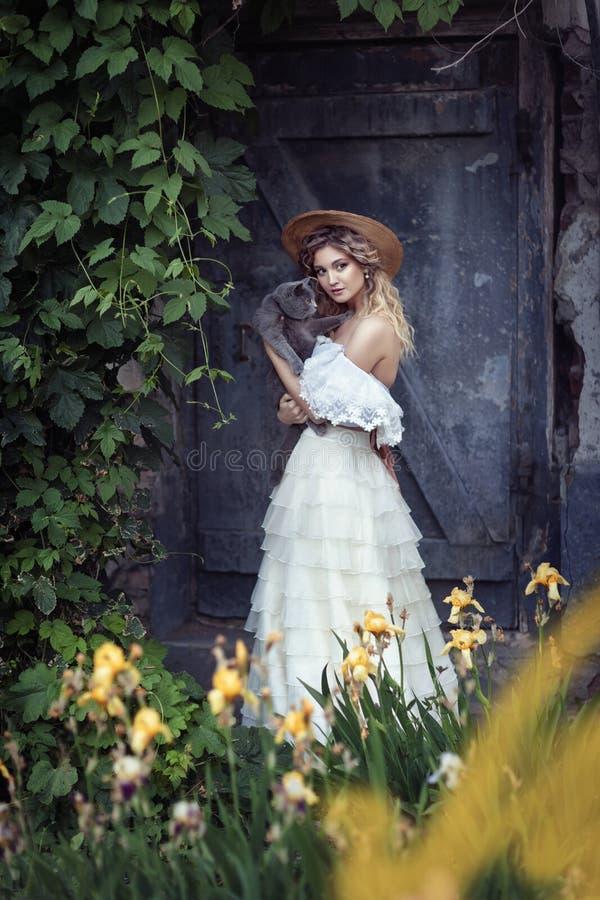 Девушка с винтажным платьем с котом стоковая фотография