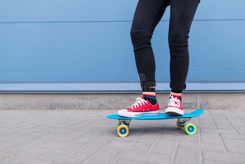 Девушка с красными парнями ехать на голубом скейтборде против предпосылки голубой стены Стиль улицы стоковое фото