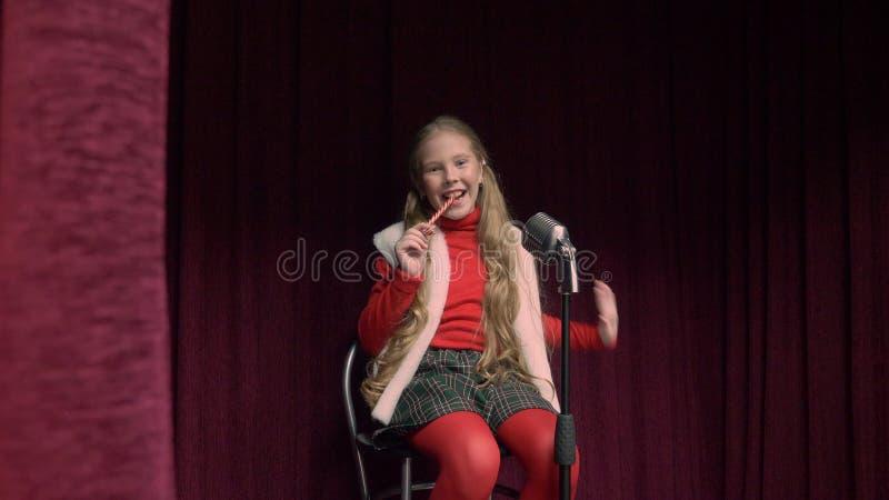 Девушка с леденцом на палочке на этапе Счастливый девочка-подросток сидя на этапе с микрофоном, поя и есть леденец на палочке стоковые фото