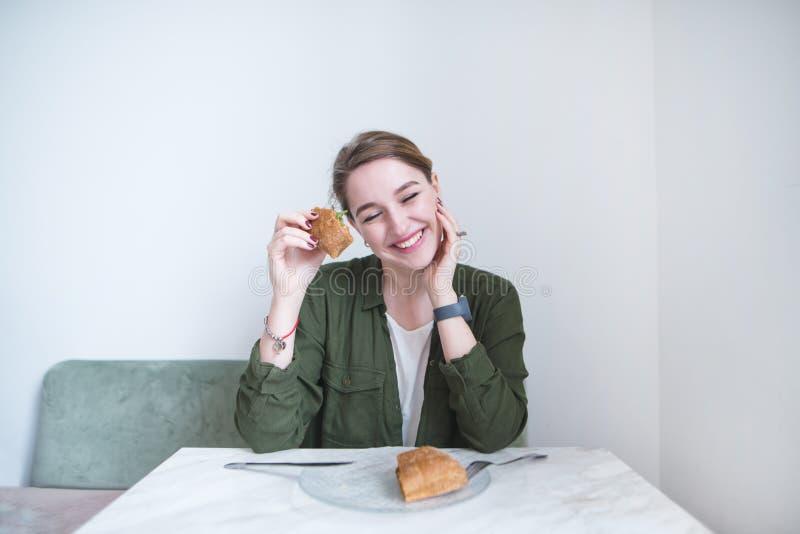 Девушка с сэндвичем в ее рук улыбках задушевно пока сидящ на таблице ресторана стоковые фотографии rf