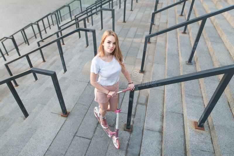 Девушка с розовым скутером пинком стоит на предпосылке современной архитектуры, взгляде камеры, взгляде сверху стоковая фотография rf
