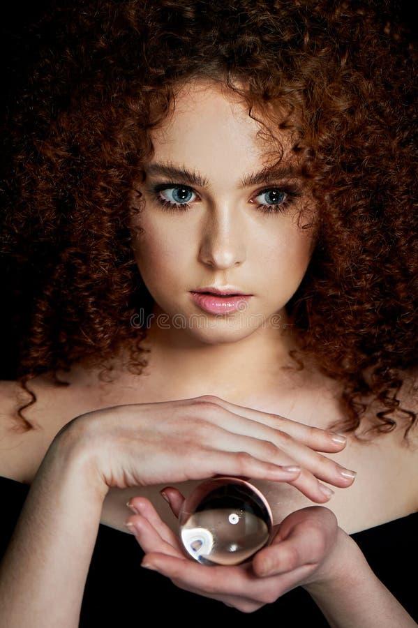 Девушка с сочными курчавыми красными волосами Владения в его руках стеклянный глобус Тайна, предчувствие будущего стоковые фотографии rf
