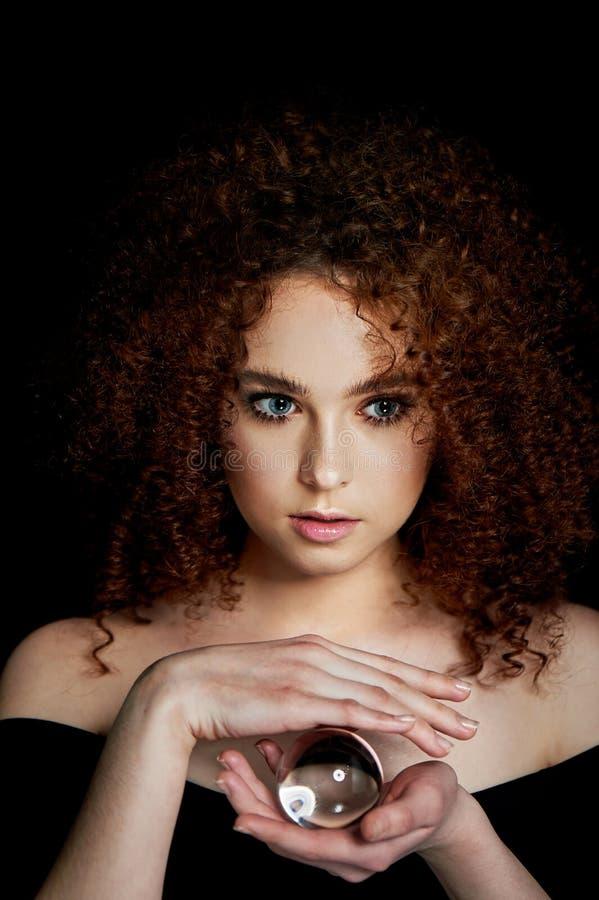Девушка с сочными курчавыми красными волосами Владения в его руках стеклянный глобус Тайна, предчувствие будущего стоковые фото