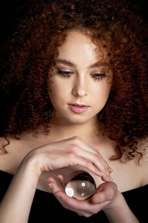 Девушка с сочными курчавыми красными волосами Владения в его руках стеклянный глобус Тайна, предчувствие будущего стоковое изображение