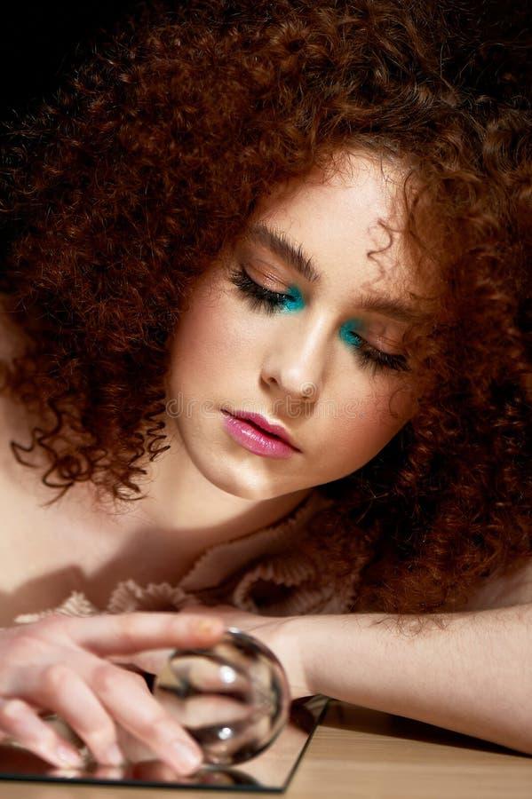Девушка с сочными курчавыми красными волосами Владения в его руках стеклянный глобус Тайна, предчувствие будущего стоковые изображения