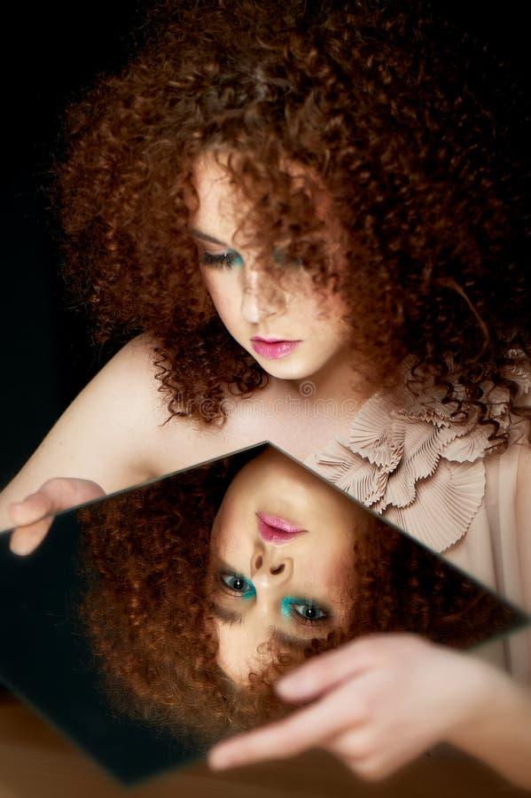 Девушка с сочными курчавыми красными волосами смотреть зеркало Тайна, предчувствие будущего его отражение внутренний взгляд стоковое изображение