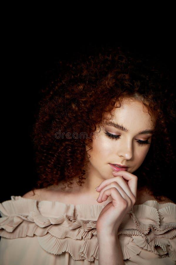Девушка с сочными курчавыми красными волосами Чувствительный макияж с ложными ресницами в стиле куклы Цвет сливк рюшей стоковая фотография