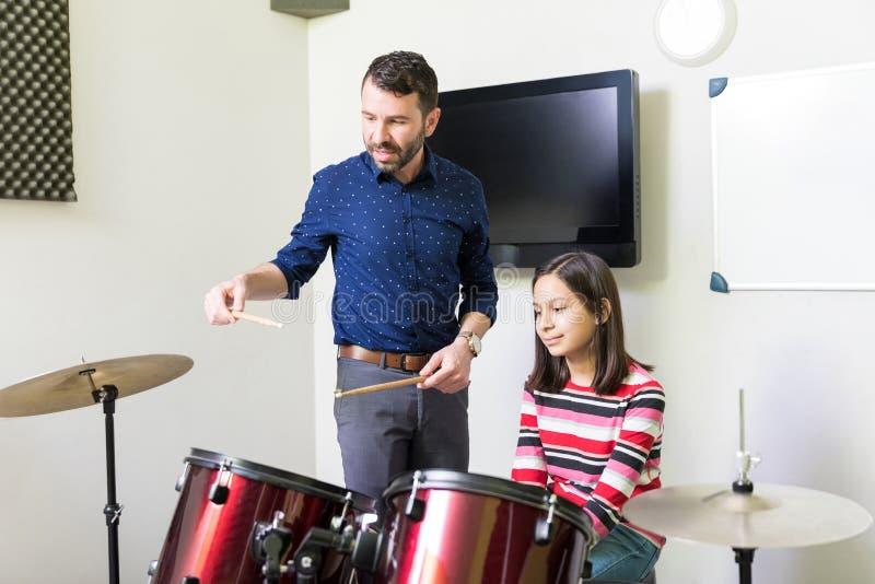 Девушка уча барабаня уроки в музыкальном классе стоковые изображения rf