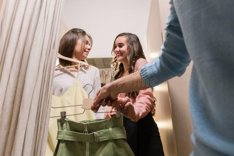 Девушки получают одежды в примерочной попробовать дальше стоковые изображения rf