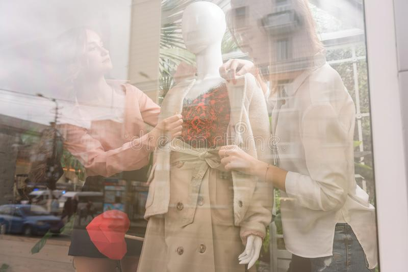 2 девушки одевают манекен на ветровом стекле магазина стоковое изображение