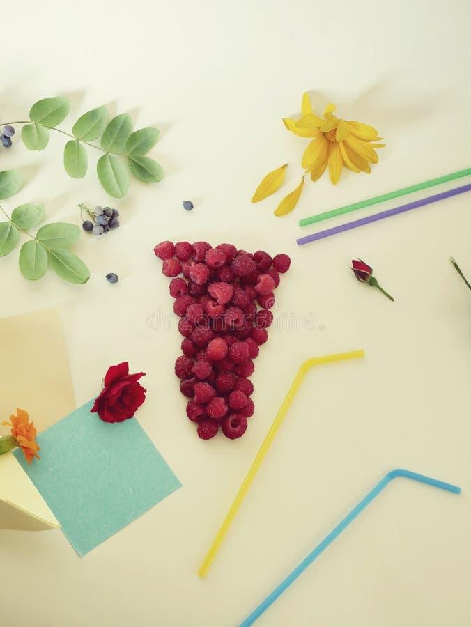 Декоративный состав - стекло свежих поленик, tubules коктейля, свежих цветков, лепестков и ягод на светлой предпосылке стоковые изображения rf
