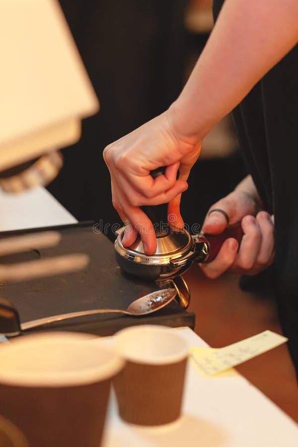 Делать кофе женщина утрамбовывает свежий земной кофе в portafilter стоковые фото