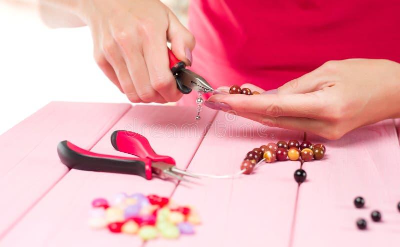 Делать ювелирных изделий Женские руки с инструментом на розовой таблице стоковое изображение rf