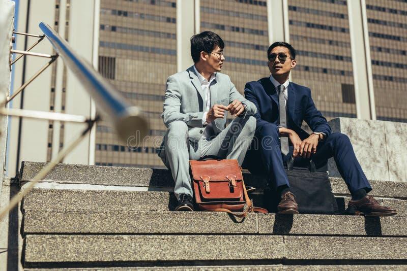 Деловые партнеры сидя на шагах outdoors и говорить стоковое изображение