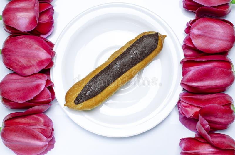 Десерт Сладкие печенья с шоколадом на белой предпосылке рядом с красочными тюльпанами стоковая фотография rf