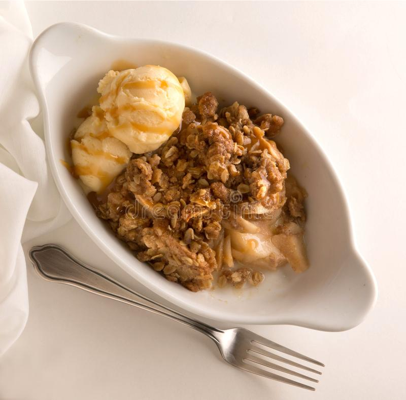 Десерт Яблока хрустящий с мороженым и карамелькой и вилкой стоковое фото